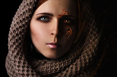 Fantasie, die Porträt eines jungen Mädchens mit einem brennenden Muster auf dem Gesicht in einem Schal auf einem schwarzen Hinter Lizenzfreie Stockfotos