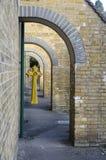 Het Keltische kruis hangt in buitenkerkarcade Stock Fotografie