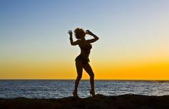 Fantasie-Schattenbild-Tänzer auf Felsen am Strand Stockfotos