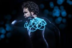 Fantasie und Zukunftsromane, schwarzer Latexmann mit blauer Neonscheibe Stockfotografie