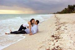 Fantasiefrau ungefähr, zum des Mannes auf Strand am sunse zu küssen Stockfotografie