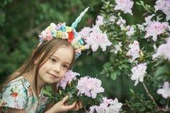 Fantasiemeisje met de hoorn van de regenboogeenhoorn met bloemen in azaleapark Voor Halloween royalty-vrije stock foto's