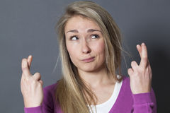 Fantasierijk blond meisje het vertrouwen op geloof in vast de kruising van haar vingers Royalty-vrije Stock Afbeelding