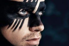 Fantasikonstmakeup man med den svart målade maskeringen på framsida tät stående upp Yrkesmässig modemakeup fotografering för bildbyråer