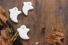 Fantasma del pan de jengibre para Halloween, adornado con las hojas de otoño, en un fondo de madera Imágenes de archivo libres de regalías