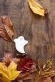 Fantasma del pan de jengibre para Halloween, adornado con las hojas de otoño, en un fondo de madera Foto de archivo libre de regalías