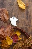 Fantasma del pan de jengibre para Halloween, adornado con las hojas de otoño, en un fondo de madera Imagenes de archivo
