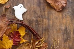 Fantasma del pan de jengibre para Halloween, adornado con las hojas de otoño, en un fondo de madera Foto de archivo