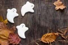 Fantasma del pan de jengibre para Halloween, adornado con las hojas de otoño, en un fondo de madera Fotos de archivo libres de regalías