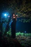 Fantasma della ragazza con gli occhi neri che stanno vicino ad un albero alla notte Giorno Halloween Immagine Stock