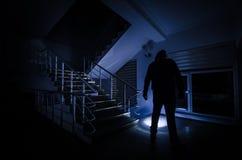 Fantasma en la casa encantada en las escaleras, silueta misteriosa del hombre del fantasma con la luz en las escaleras, escena de imagen de archivo