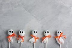 Fantasmas do pirulito de Dia das Bruxas no fundo concreto cinzento Fotografia de Stock