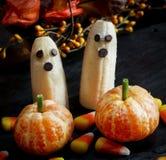 Fantasmas e Clementine Pumpkins da banana do alimento de Dia das Bruxas no fundo assustador escuro Imagens de Stock