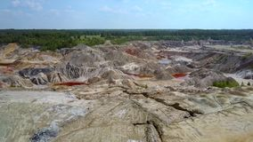 Aerial space landscape of abandoned clay pit under blue sky. Fantastic aerial space landscape of huge abandoned clay pit against boundless green forest under stock video footage