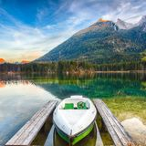 Fantastic autumn evening at Hintersee lake. Few boats on the lak. E with turquoise water of Hintersee lake. Location: resort Ramsau, National park stock image