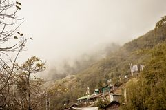 Fantastic beauty of town in hill slope of himalayas mountain, Dramatic cliffs surrond the town in a foggy winter day. Darjeeling stock photography