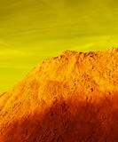 Fantastic, bright picture and twist sur. Mountain on a background sky syurrialisticheskogo, stones and sand stock photography