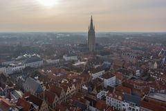 Fantastic Bruges city skyline with red tiled roofs and Church of Our Lady tower in winter day. View to Bruges medieval cityscape. From the top of the Belfry royalty free stock images