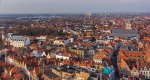 Fantastic Bruges city skyline with red tiled roofs and St. James`s Church Sint-Jakobskerk in sunny winter day. View to Bruges. Medieval cityscape from the top royalty free stock images