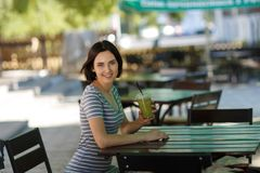 Positive girl with a smoothie. Smiling woman sitting at the blurred cafe background. Outdoors cafe concept. Copy space. Stock Images