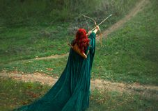 Fantastic character, bright photo, the best woman shooter bravely and courageously goes hunting, red-haired girl is. Preparing to shoot an arrow from a bow royalty free stock photos