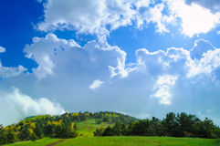Fantastic Cloudy Sky over the Forest and Hill Stock Image