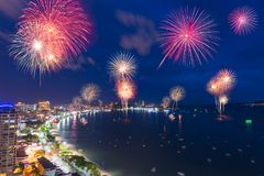Fantastic and colorful fireworks over the sea and city royalty free stock images