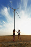 Girls walking next to a windmill. Electric windmill in the field on a sunny sky background. Youth concept. Copy space. Fantastic, cute, natural girls walking in Royalty Free Stock Photo