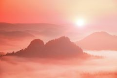 Fantastic dreamy daybreak above peaks of smoky mountain with the view into misty valley Royalty Free Stock Photo