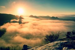 Fantastic dreamy sunrise on the top of the rocky mountain with the view into misty valley Stock Images