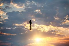 Fantastic fantasy photo. A woman in a black cape walking in the sky. stock image