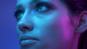 Fantastic fashion model with glitter eye-shadows in colorful neon lights watches in puzzlement on the surroundings. Fantastic fashion model with glitter eye stock footage
