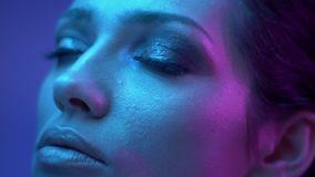 Fantastic fashion model with glitter eye-shadows in colorful neon lights watches upwards dreamily. Fantastic fashion model with glitter eye-shadows in colorful stock footage