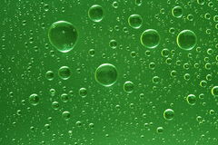 Fantastic green drops of water on glass Royalty Free Stock Image