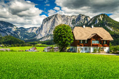 Fantastic green fields with alpine houses and mountains, Altaussee, Austria. Amazing summer landscape with green fields, alpine farmland, pasture and high rocky stock photos