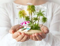 Fantastic island. Small fantastic island with sunbeds and palms in women's hands. Tropical vacation stock images