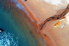 Ilhabela, Brazil: Aerial view of a beautiful beach with red sand and surf board. stock photo