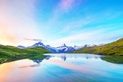 Fantastic landscape at sunrise over the lake in the Swiss Alps, Europe. Wetterhorn, Schreckhorn, Finsteraarhorn et Bachsee. Relaxation, harmony, anti-stress stock photo