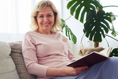 Fantastic madam smiling while reading book Stock Photos