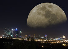 Fantastic Moscow night moon. Fantastic cityscape: night city-line panorama of Moscow with modern and old buildings, streets, lights and huge arising moon on dark Stock Photography