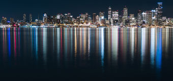 Fantastic nighttime panoramic city view with illuminated skyscrapers reflected on calm water. Stock Images
