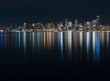 Fantastic nighttime panoramic city view with illuminated skyscrapers reflected on calm water. Stock Image