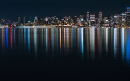 Fantastic nighttime panoramic city view with illuminated skyscrapers reflected on calm water. Royalty Free Stock Photo