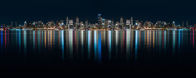 Fantastic nighttime panoramic city view with illuminated skyscrapers reflected on calm water. Royalty Free Stock Photos