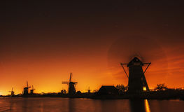 Fantastic orange sunset traditional Dutch windmills canal in Rot Stock Image