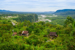 Fantastic overview of amazon jungle valley with river and waterfalls in the distance, some simple small houses located. Sorrounded by forest stock photography