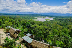 Fantastic overview of amazon jungle valley with river and waterfalls in the distance, some simple small houses located. Sorrounded by forest royalty free stock photography