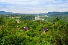 Fantastic overview of amazon jungle valley with river and waterfalls in the distance, some simple small houses located. Sorrounded by forest royalty free stock images