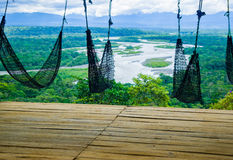 Fantastic overview from hammocks terrace of amazon jungle valley with river and waterfalls in the distance, some simple. Small houses located sorrounded by royalty free stock photos