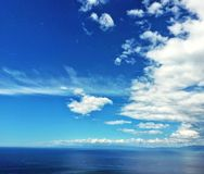 FANTASTIC PANORAMIC VIEW WITH BLUE SKY AND SEA AND WHITE CLOUDS Royalty Free Stock Photography
